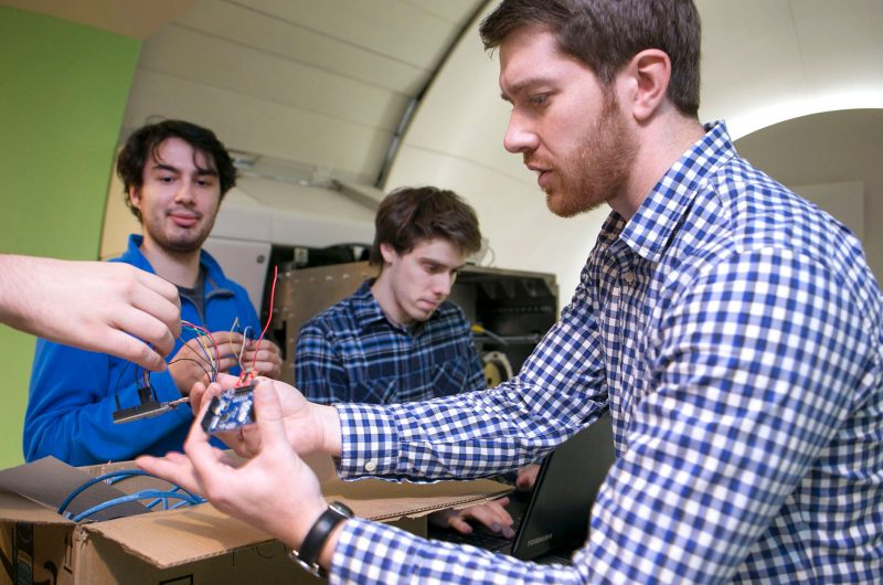 Marc Costantine (right) of Orbital ATK advises Virginia CubeSat Constellation student team members from UVA David Khannan (left) and Michael Ford (center) on test set up.